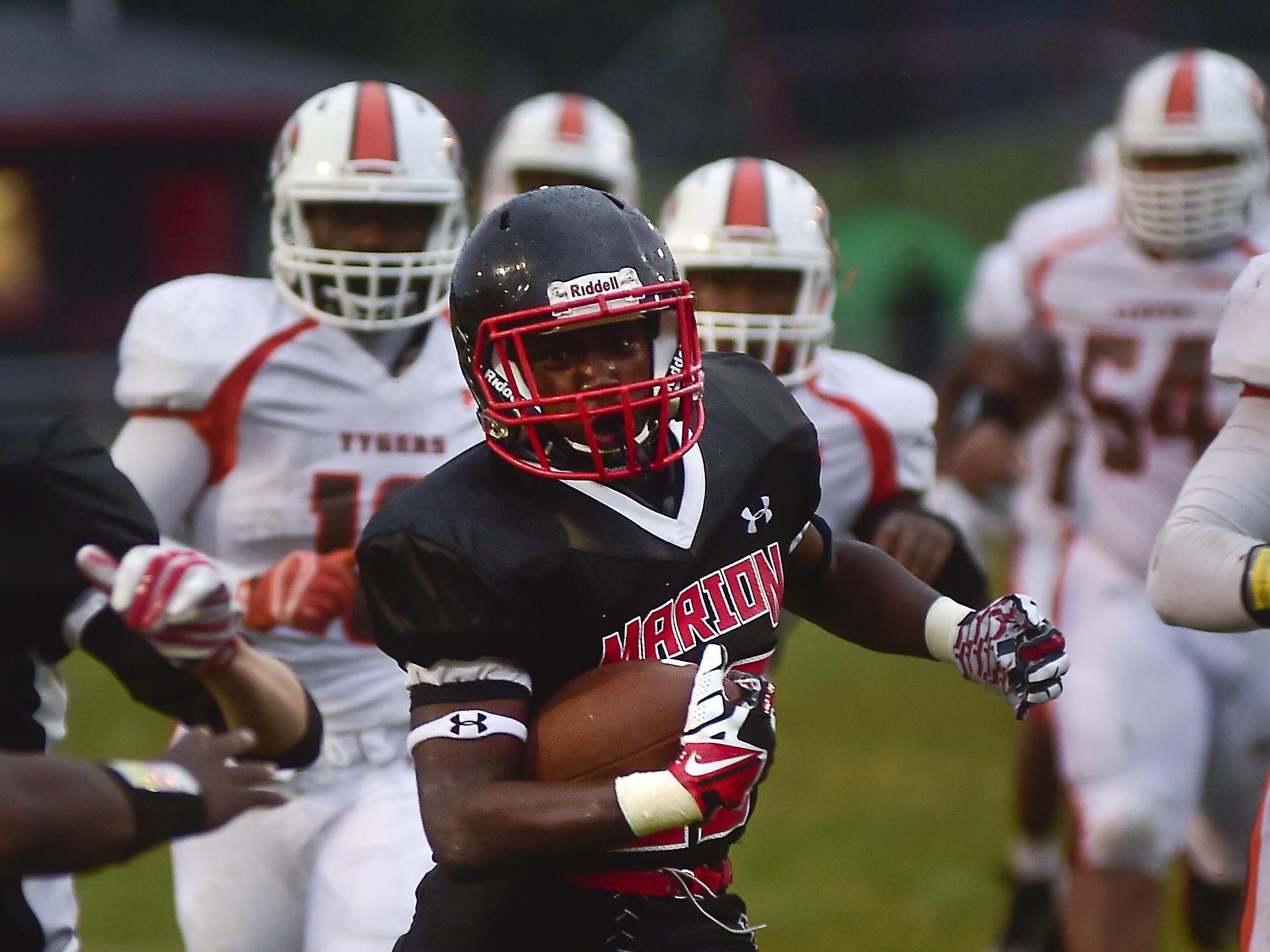 Marion Harding's Titus Douglas gains yards as he eludes Mansfield Senior players during the Harding vs Mansfield Senior football game on Friday.