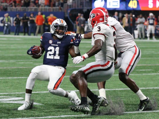 Auburn running back Kerryon Johnson is stopped by Georgia linebacker Roquan Smith (3) during the SEC title game at Mercedes-Benz Stadium, Dec. 2, 2017, in Atlanta.