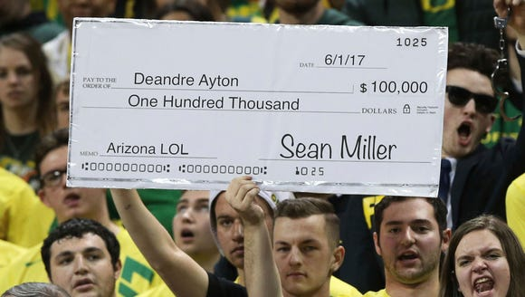 Fans in the Oregon student section hold up a sign making