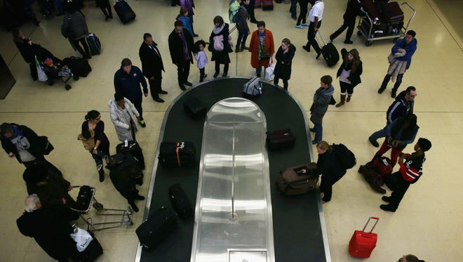 Travelers wait for their luggage after arriving at Washington Reagan National Airport on Nov. 26, 2014.
