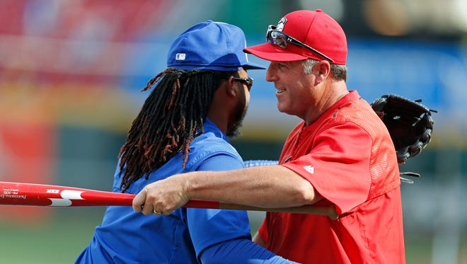 Kansas City Royals pitcher Johnny Cueto, left, hugs Cincinnati Reds manager Bryan Price before a baseball game, Tuesday, Aug.18, 2015, in Cincinnati. Cueto was traded to the Royals from the Reds in July.