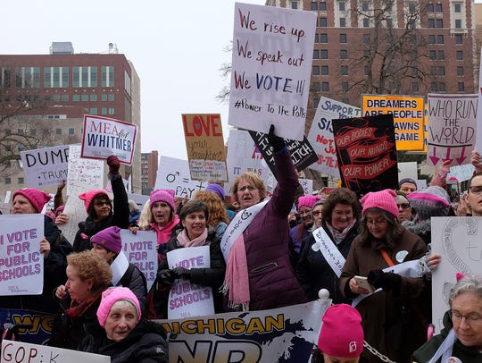 People attend a women's march in Lansing, Mich., on