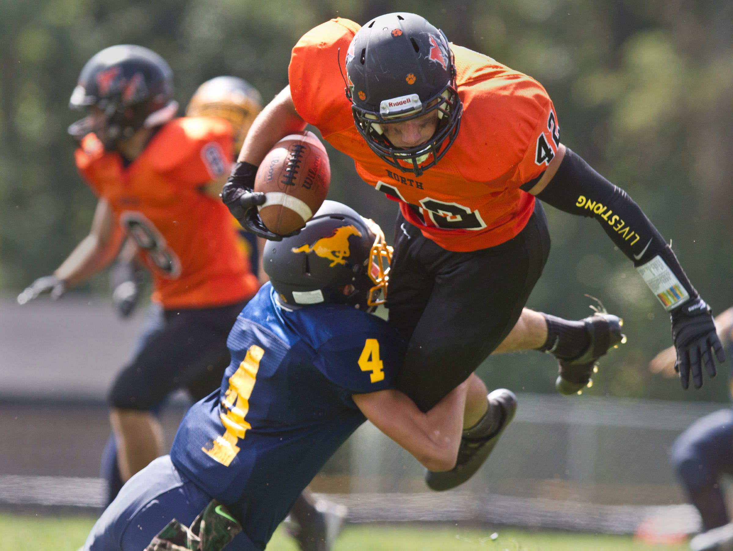 Middletown North's Chad Freshnock tries to jump over Marlboro's Chris Ottaviano Middletown North vs Marlboro football. Marlboro, NJ Saturday, September 19, 2015 @dhoodhood