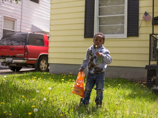 Sincere Smith blows on a dandelion while visiting a family friend's house in Flint's east side on Wednesday May 10, 2017. Their family moved out of the city of Flint in 2016 after Sincere developed severe rashes his mother believed were the result of bathing in the contaminated water during the Flint water crisis.