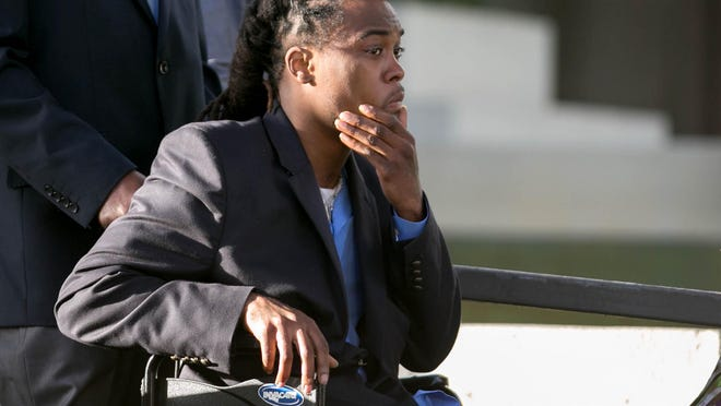 Dontrell Stephens looks up as he exits the federal courthouse in Fort Lauderdale after a jury awarded him $23.1 million in a civil suit involving Palm Beach County Sheriff's Deputy Adams Lin. Stephens was shot by Lin in September 2013 after being stopped for riding his bicycle erratically.