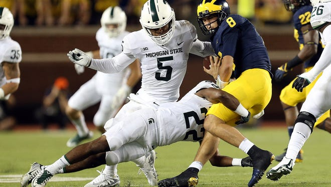 Michigan QB John O'Korn (8) is sacked by Michigan State CB Josiah Scott (22) during first half action in a game between MSU and U-M at Michigan Stadium in Ann Arbor on Sat., Oct. 7, 2017.