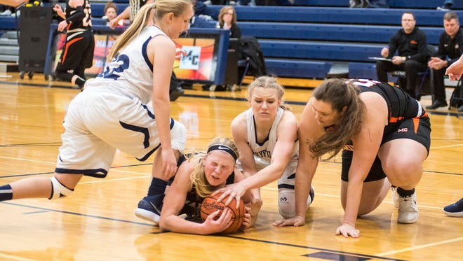 Marine City's Erin Davis (center) struggles to hold the ball while Marysville's Alisyn Hall (32) and Hayley Delor try to steal it during the MHSAA Class B District Championship at Marysville High School Feb. 28.