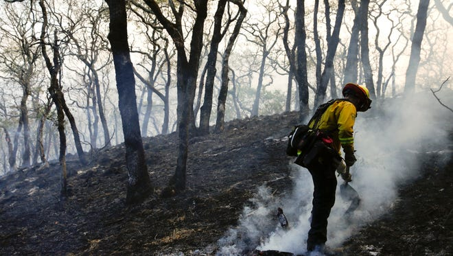 A firefighter mops up the area scorched by a wildfire Saturday in Santa Rosa. More than 10,000 firefighters have been deployed to battle the Northern California wildfires.