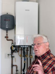 Donald Bahnck of Berkeley stands before his new combination gas boiler and water heater.