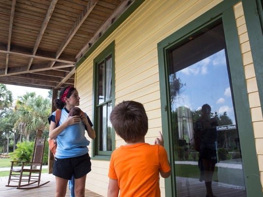 Brooklyn Cahill, 23, left, of Fort Myers, looks at a grasshopper with her daughter Ophelia Cahill, 1 month, and stepson Landon Cahill, 6, at the Koreshan State Historic Site in Estero, Florida, on July 27, 2016. The site contains areas of pine flatwoods habitat, a nature walk and the settlement of a religious colony, the Koreshan Unity, whose last members deeded the land to the state in 1961.