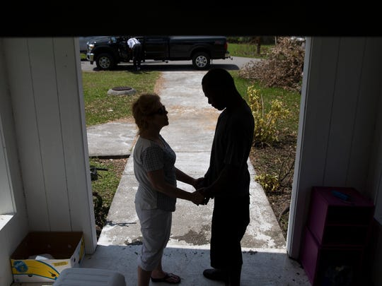 Michelle-Ruth Haskins, of Naples, prays with Daniel Burgess Sr., a Copeland resident, in the entrance of Copeland Baptist Church Tuesday, September 19, 2017 in Copeland, Fla. Just over a week after Hurricane Irma passed over Southwest Florida the small rural town of Copeland, Fla., located just north of Everglades City on State Highway 29, is still struggling without power, resources, and any sign of help on its' way.