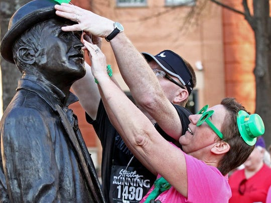Greg and Koleta Thomsen of Anderson decorate the William Whitner statue with a green hat before the St. Patrick's Day in the Electric City event in downtown Anderson.