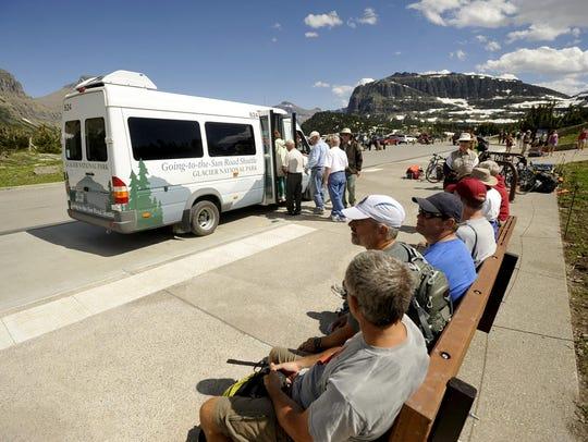 Glacier Park visitors wait for the shuttle at Logan