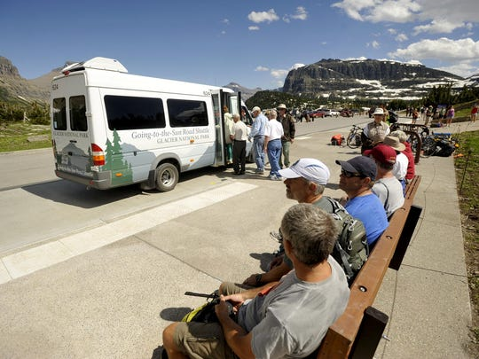Glacier Park visitors wait for the shuttle at Logan