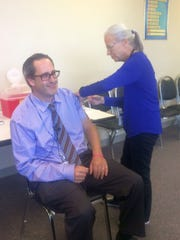 Cindy Trick, public health nurse with the Brown County Health Department, gives a flu shot to Brown County Executive Troy Streckenbach during the kickoff of County Public Health Week on Monday at the department office in Green Bay.