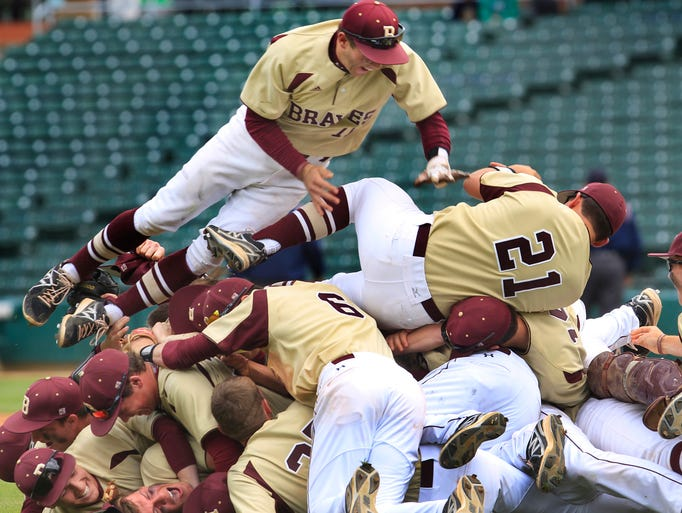 Brebeuf Braves players jump on each other after defeating North Central 5-2 in the County baseball tournament at Victory Field in Indianapolis on Saturday, May 17, 2014. Down 2-1 in the bottom of the fifth, the Braves scored all four of their runs in the inning for the victory.