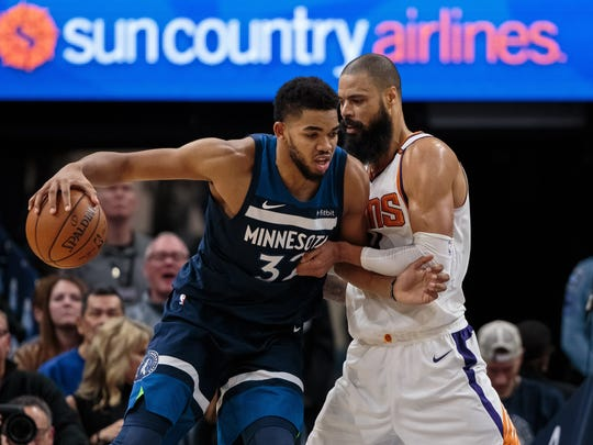 Timberwolves center Karl-Anthony Towns dribbles against the Suns' Tyson Chandler.