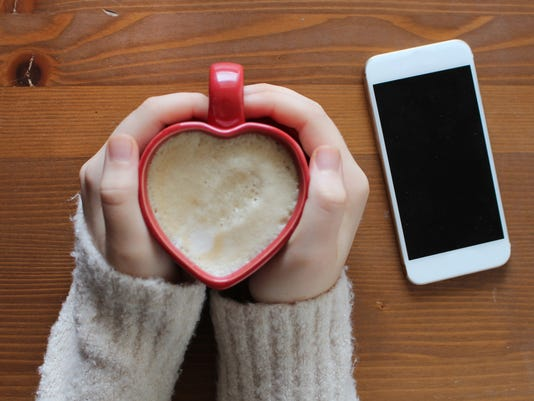 Young woman holding a heart shaped coffee cup on wooden background