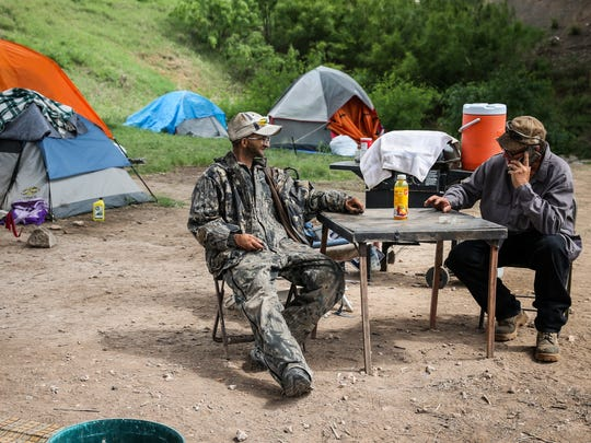 Reggie Felton hangs out as Mike Brannon talks on the phone with a potential employers outside of his tent under the Houston Harte Expressway in San Angelo.