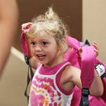 Brilea Hayes, 4, puts on her new backpack at Victory Mission's 26th annual Back to School event on August 4, 2015.