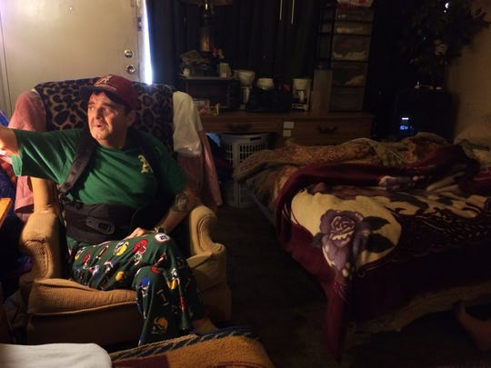 """In this Jan. 29, 2016 photo, Steven Gibbs, 61, sits in the motel room he shares with his wife, Debbie, and their daughter and son-in-law in Murfreesboro, Tenn. """"Half the time I'm scared to go outside the door,"""" says Gibbs, 61, a former construction worker who has been jailed twice since late 2013 after he couldn't pay hundreds of dollars in probation fees for driving on a suspended license. Despite a court order barring the county and a private probation company from jailing him again, those fears linger."""