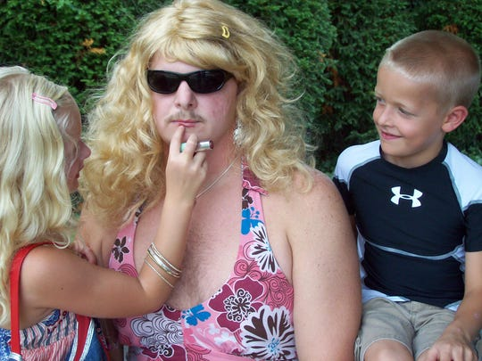 Tony Tirey gets help from his children, Emily, 6, and Brandon, 7, in getting into character as Faith Hill for the 2008 game.