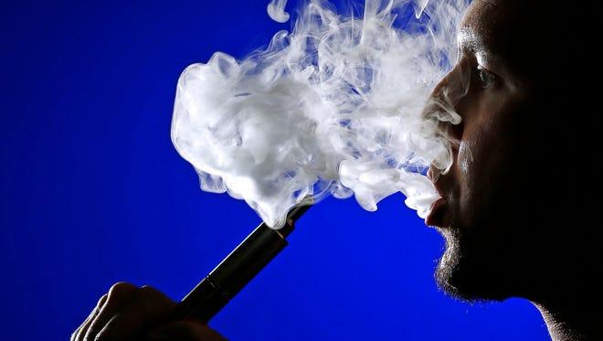 """Matt Berger, owner of e-cigarette retailer """"Butt Out,"""" exhales a cloud of vapor."""