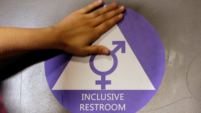 In this May 17, 2016 file photo, a new sticker is placed on the door at the ceremonial opening of a gender neutral bathroom at Nathan Hale High School in Seattle.
