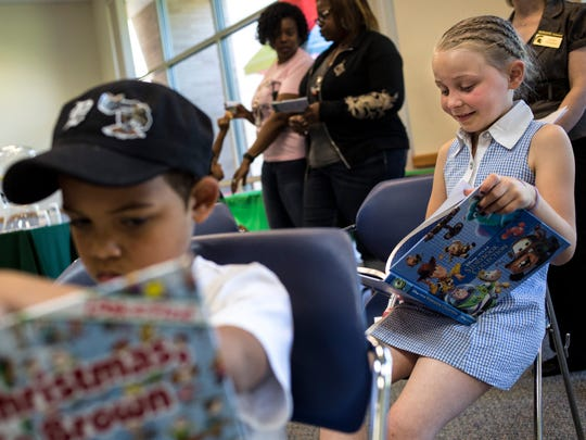 Adrianna LaCroix, 8, and Jamal Waldon, 7, of Port Huron, read books during the Juneteenth celebration Friday, June 17, 2016 at the Donald Dodge auditorium in the St. Clair County Administrative Building in Port Huron.