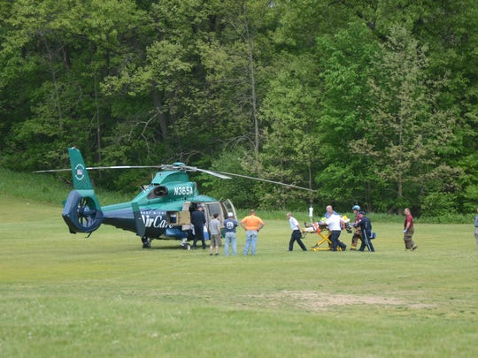 Rescue workers take the injured Pennfield girl to a waiting AirCare medical helicopter.