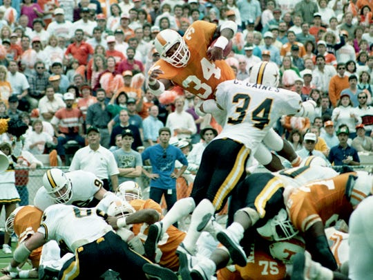 Tennessee tailback Reggie Cobb (34) is grabbed by Vanderbilt linebacker Chris Gaines (34) as he attempts to dive over the goal line for a touchdown during second-quarter action. Tennessee pulled out a 38-36 victory over Vanderbilt before 93,306 at Neyland Stadium in Knoxville on Nov. 28, 1987.