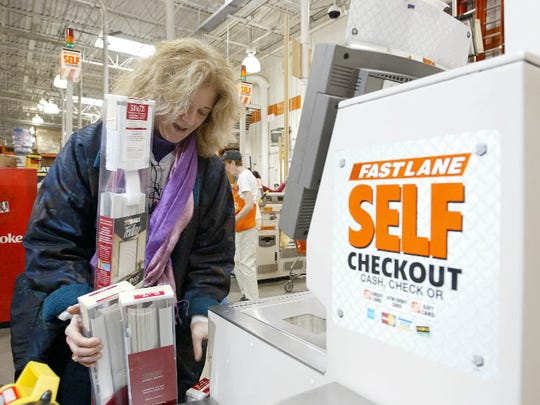 Shirley Cook of Philadelphia buys four packages of mini-blinds at the self service check out at a Home Depot store in Philadelphia, PA on April 15, 2004.