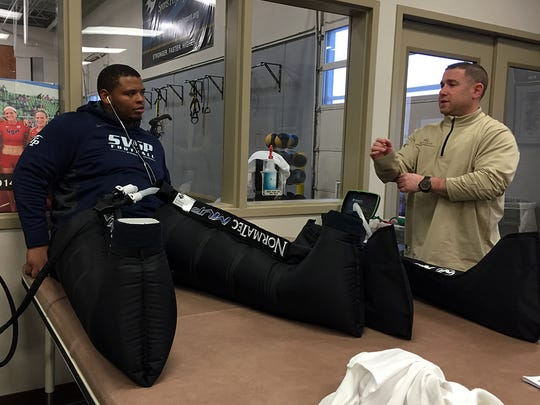 "Agent Andrew ""Buddy"" Baker talking with client Deon Simon, a defensive lineman from Northwestern State. Simon was using compression boots for muscle recovery at St. Vincent Sports Performance."