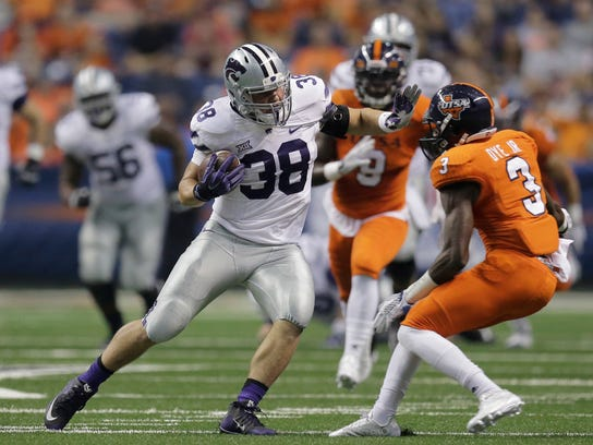 File-This Sept. 12, 2015, file photo shows Kansas State Wildcats's Winston Dimel (38) looking to evade UTSA's Stanley Dye Jr. (3) after making a catch during the first half on an NCAA college football game, in San Antonio.  Dimel is back after he ran for 12 TDs a year ago. (AP Photo/Eric Gay, File)