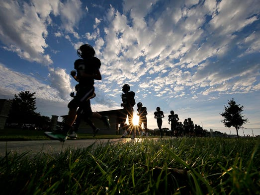 Wauwatosa West Football Players jog off the field after
