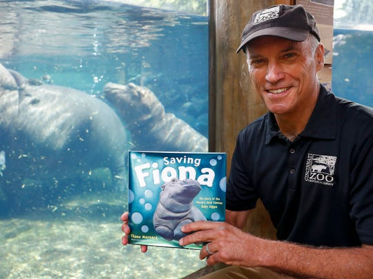 In this Tuesday, June 26, 2018 photo, Cincinnati Zoo & Botanical Garden Thane Maynard poses for a photograph beside the enclosure of Fiona, their baby Nile Hippopotamus, in Cincinnati. The Cincinnati Zoo's globally famous premature hippo does more than help sell T-shirts, bobbleheads and ice cream. She is becoming a teaching tool in classrooms and libraries and subject of a series of books with the latest by Maynard. (AP Photo/John Minchillo)