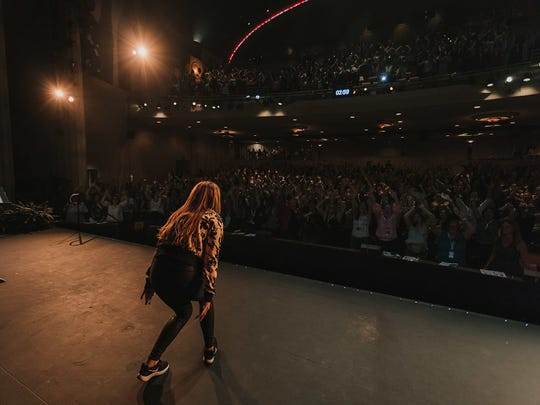 "Rachel Hollis - a speaker known as ""the Tony Robbins for women"" - speaks to a group of women during a RISE conference to get them to know that they can change the world."