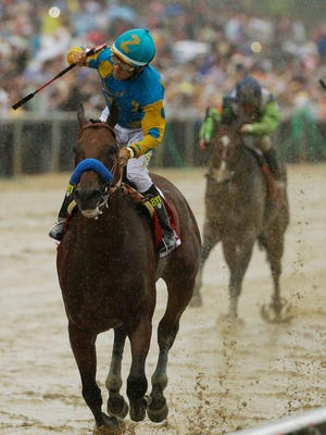 American Pharoah, ridden by Victor Espinoza, left, wins the 140th Preakness Stakes horse race at Pimlico Race Course.