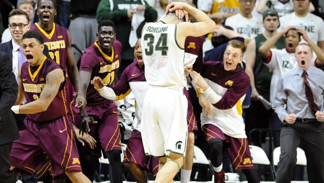 The Minnesota bench celebrates in front of a dejected Gavin Schilling after Schilling fouled Minnesota's Carlos Morris as Morris hit a 3-point shot to tie the game in the final seconds of regulation.