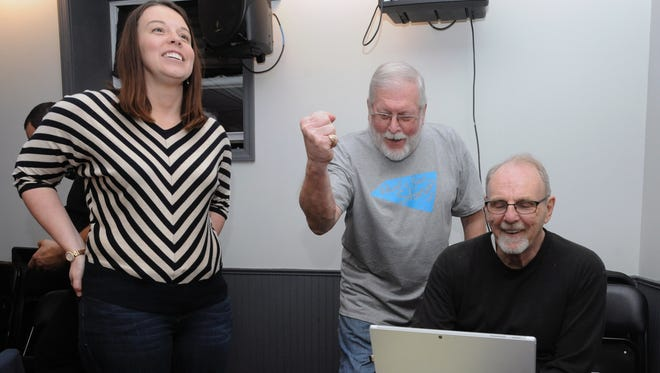 Leia Snyder, superintendent, left, Mike Thompson, Ross County Board of Developmental Disabilities president, center, and Rick Marriott, levy chairman, celebrate as results come in Tuesday evening at the Dock.