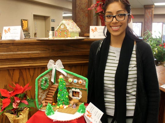 Angela Condito stands with 'Twas the Night Before Christmas, the gingerbread house she created on behalf of the Salvation Army.