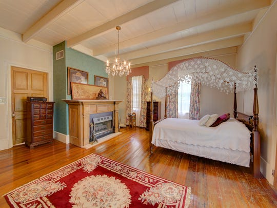 A bedroom in the home is furnished with antique pieces.