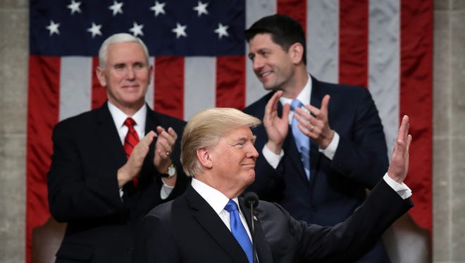 President Donald Trump waves during the State of the Union address as Vice President Mike Pence (l) and house speaker Paul Ryan look on in the chamber of the US House of Representatives in Washington on Tuesday. L