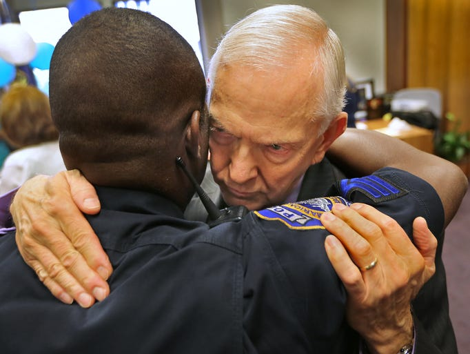 IMPD chaplain Philip Bacon, right, hugs IMPD well-wisher Sgt. Michael Jefferson, during his retirement reception at the City/County Building Tuesday, July 29, 2014.  Bacon was a chaplain with IPD and IMPD for 23 years.