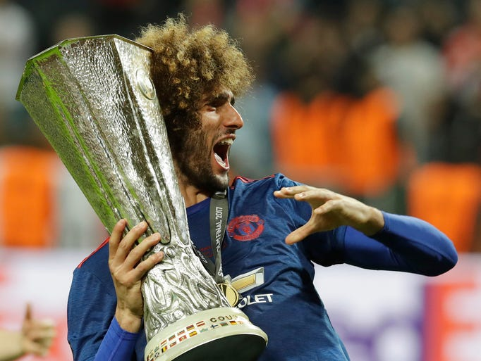 Manchester's Marouane Fellaini holds the trophy after