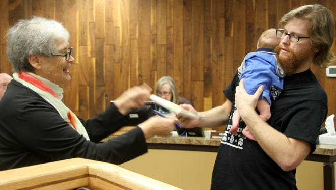 Doris Bruton-Carleton presented the first book of the new initiative to 4-month-old Magnus and his father, Vincent Voris.