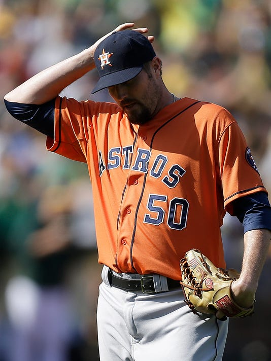 Houston Astros' Chad Qualls adjusts his cap in the ninth inning of a baseball game against the Oakland Athletics Saturday, April 19, 2014, in Oakland, Calif. The A's won 4-3. (AP Photo/Ben Margot)