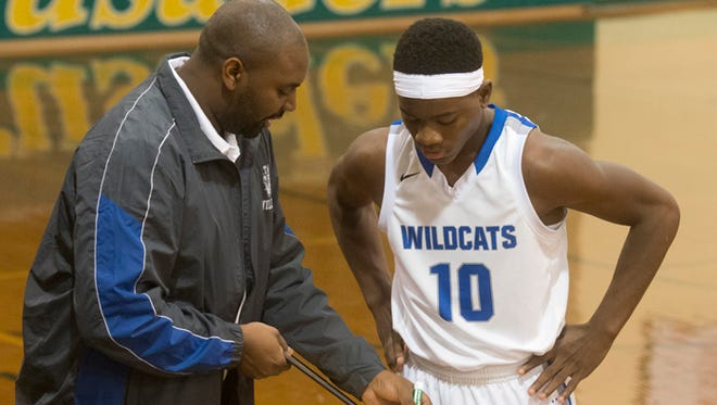Washington High School basketball coach Justin Pierce, left, gives Garry Lawrence (No. 10) a few pointers during a break in the game against Sheridan Hills in the Catholic Crusaders Christmas Classic Monday night.