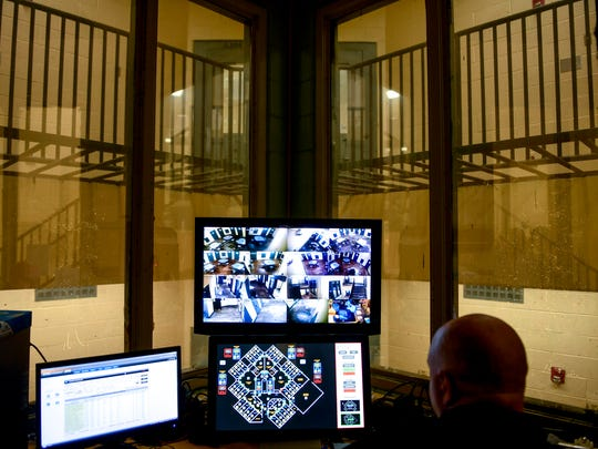 A correctional officer can be seen watching the monitors that give him a glimpse into all the cells of one of the pods at Madison County Jail in Jackson, Tenn., on Wednesday, Aug. 29, 2018.