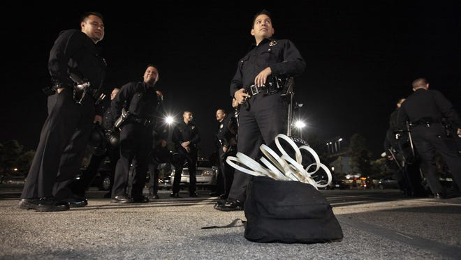 Los Angeles Police Department officers wait to board buses headed to the Occupy Los Angeles encampment.